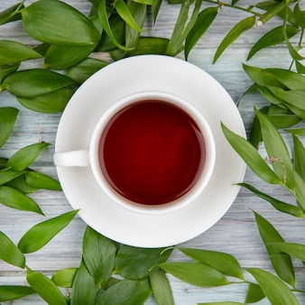 Vista dall'alto di una tazza di tè con foglie verdi su legno grigio