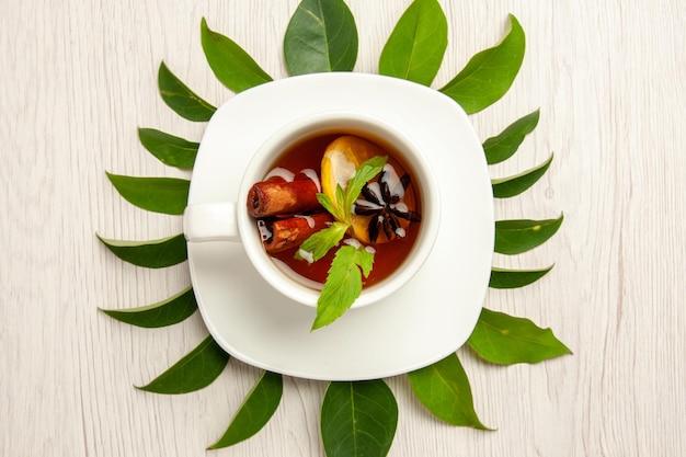 Vista dall'alto tazza di tè con foglie verdi sulla cerimonia della frutta del tè colore scrivania bianca