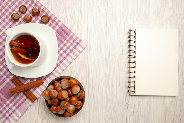 Vista dall'alto tazza di tè con nocciole e cannella sul colore bianco dello spuntino del tè del dado della scrivania