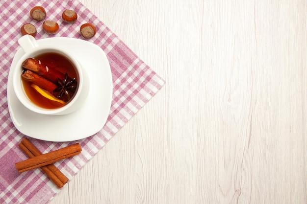 Vista dall'alto tazza di tè con nocciole e cannella su scrivania bianca cerimonia di spuntino con noce di tè noce
