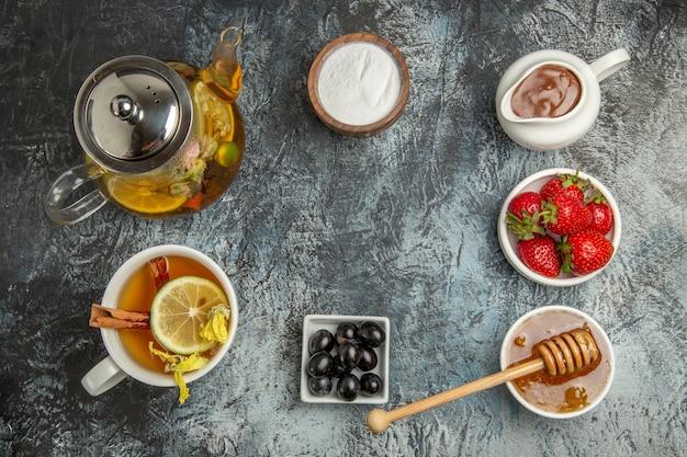 Vista dall'alto tazza di tè con miele e frutta sul tè alla frutta dolce superficie leggera