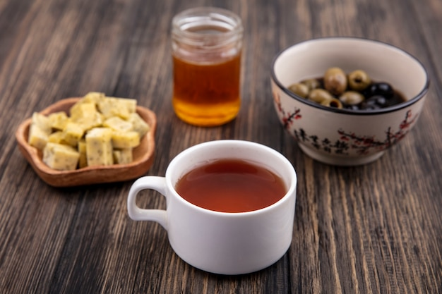 Top view of a cup of tea with honey with olives and chopped slices of cheese on a wooden background