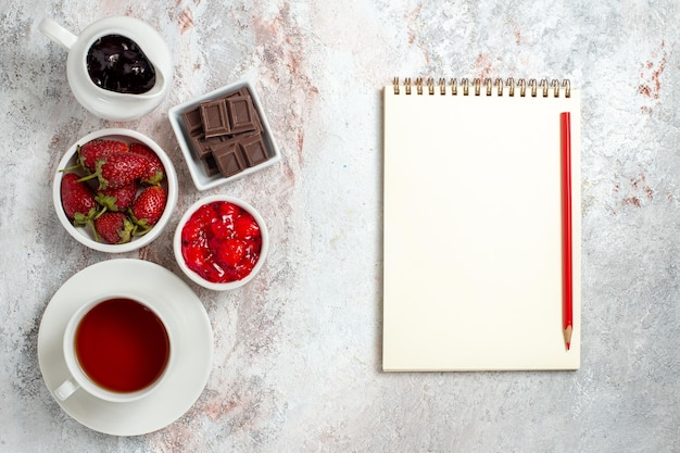Top view of cup of tea with jam and chocolate on a white surface