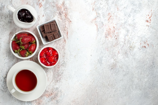 Top view of cup of tea with jam and chocolate on white surface