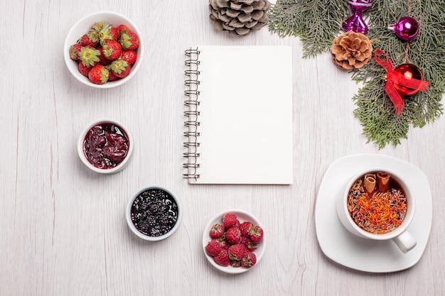Vista dall'alto tazza di tè con marmellata e frutta sul tavolo bianco colore gelatina di tè alla frutta