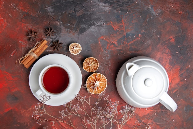 Top view cup of tea with kettle on dark table