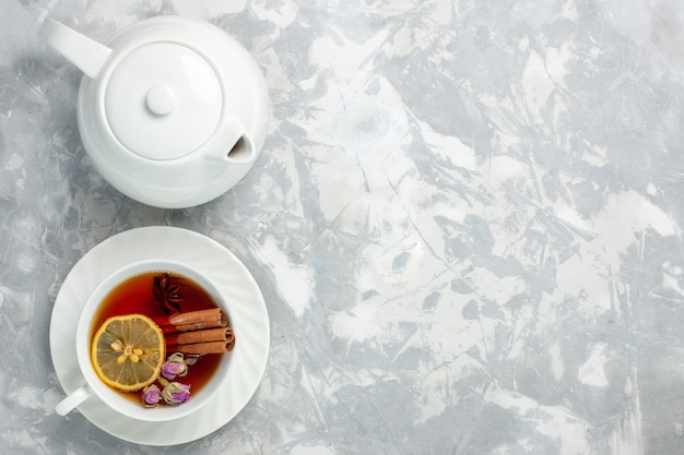 Top view cup of tea with lemon and cinnamon on light white surface