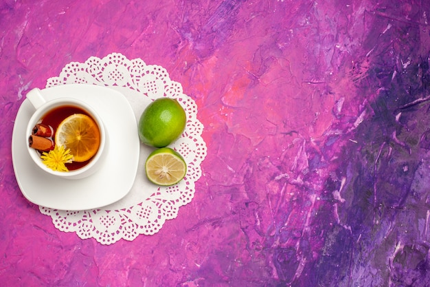 Top view cup of tea with lemon and cinnamon on pink floor candy color tea