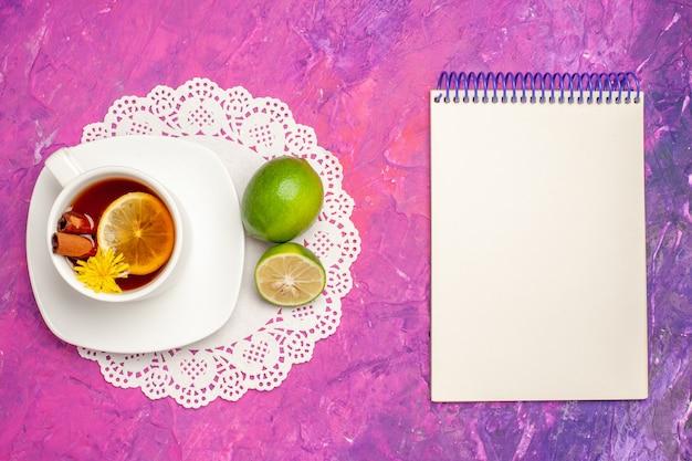 Vista dall'alto tazza di tè con limone e cannella sul tavolo rosa tè color caramella