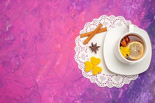 Vista dall'alto tazza di tè con limone e cannella su caramelle color tè da tavola rosa