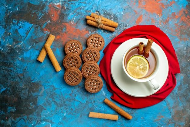 Vista dall'alto tazza di tè con biscotti scialle rosso limone e cannella su superficie rossa blu