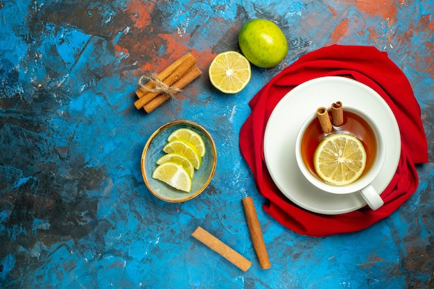 Top view cup of tea with lemon and cinnamon red shawl on blue red surface copy place