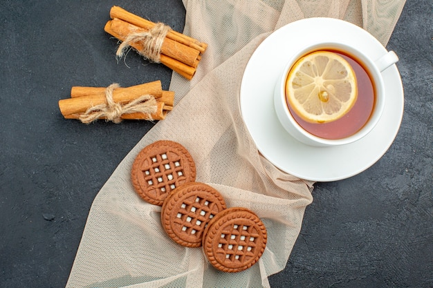Top view a cup of tea with lemon cinnamon sticks cookies on beige shawl on dark surface