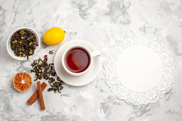 Vista dall'alto tazza di tè con limone e cannella su uno spazio bianco