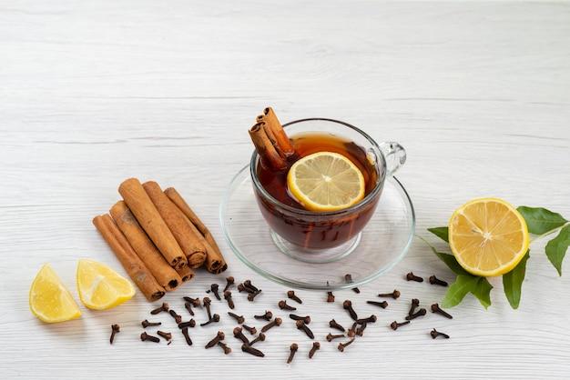 Una tazza di tè con vista dall'alto al limone e cannella su bianco, caramelle da dessert al tè