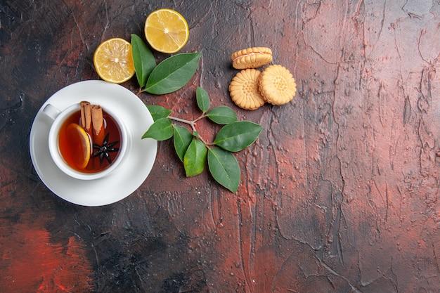 Vista dall'alto tazza di tè con limone e biscotti sulla torta biscotto dolce tavolo scuro