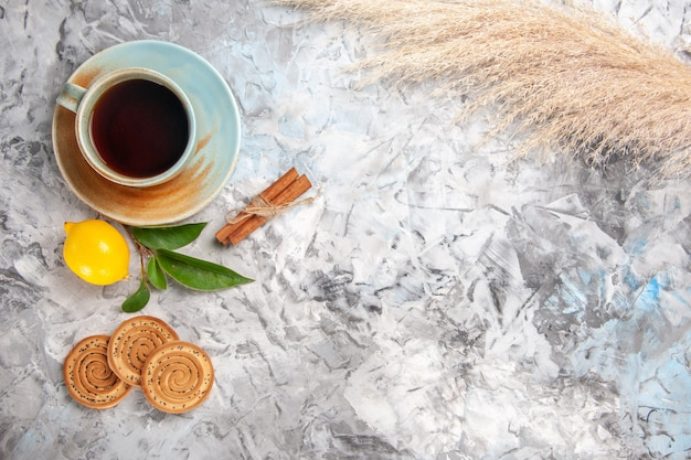 Top view cup of tea with lemon and cookies on white table fruit tea drink