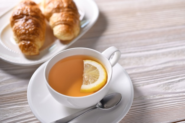 Top view of a cup of tea with lemon and croissant on white table