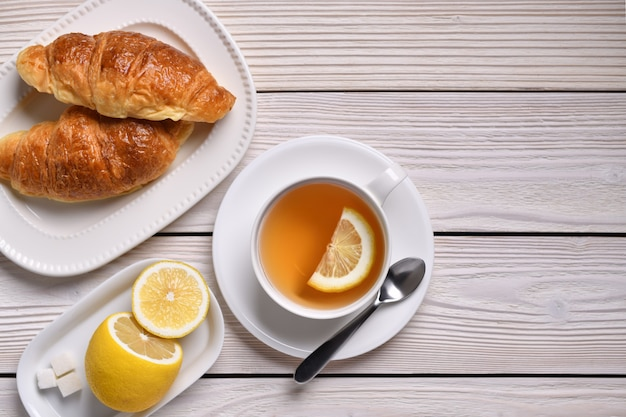 Top view of a cup of tea with lemon and croissants on white table