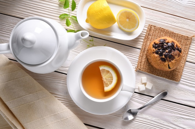 Top view of a cup of tea with lemon and cupcake on white table