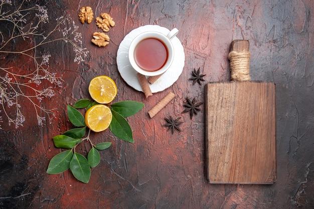Top view cup of tea with lemon on dark table tea dark fruit