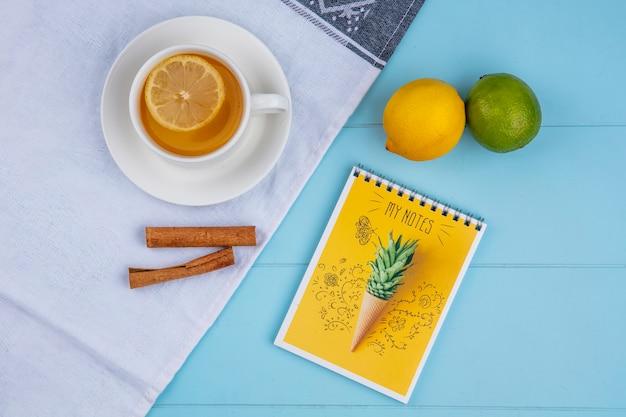 Vista dall'alto della tazza di tè con limone e calce cannella su un asciugamano bianco con un taccuino su una superficie blu