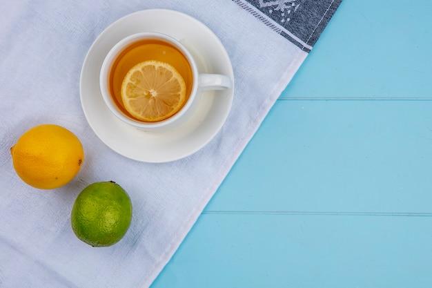 Vista dall'alto della tazza di tè con limone e lime su un asciugamano bianco su una superficie blu