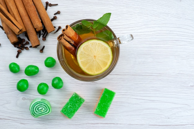 Una tazza di tè con vista dall'alto con menta al limone e cannella su bianco, caramelle da dessert al tè