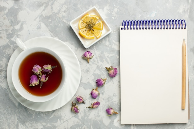 Top view cup of tea with lemon and notepad on the white desk