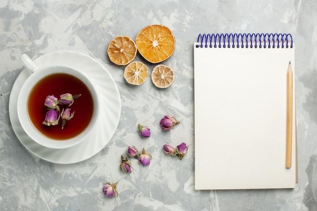 Vista dall'alto tazza di tè al limone e blocco note sulla scrivania bianca