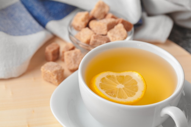 Top view of a cup of tea with lemon piece on wooden table