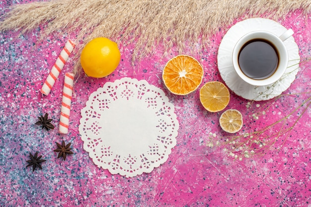 Top view of cup of tea with lemon on pink surface