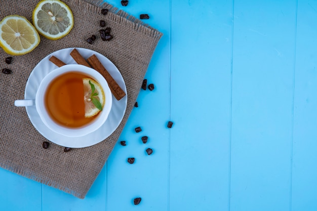 Top view of cup of tea with lemon slice and cinnamon on saucer with lemon slices and chocolate pieces on sackcloth on blue background with copy space