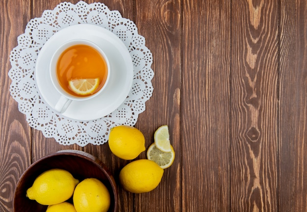 Top view of cup of tea with lemon slice in it on paper doily and lemons on left side and wooden background with copy space