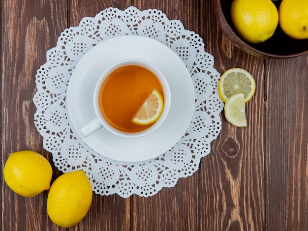 Top view of cup of tea with lemon slice in it on paper doily and lemons on wooden background