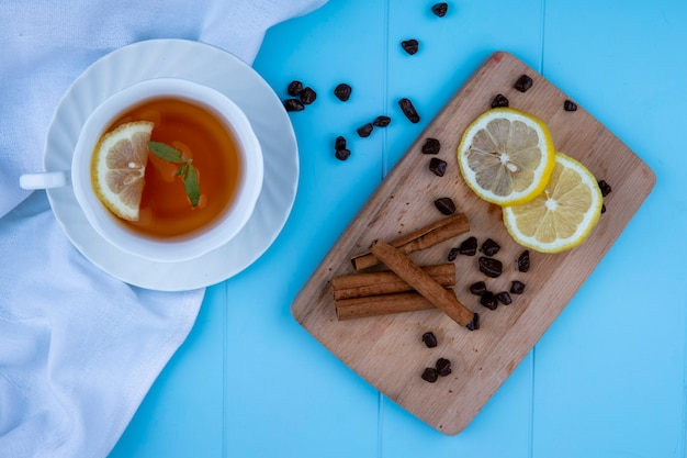 Top view of cup of tea with lemon slice on white cloth and cinnamon with lemon slices and chocolate pieces on cutting board on blue background
