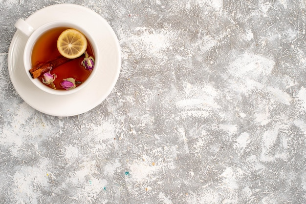 Top view of cup of tea with lemon slice on white surface