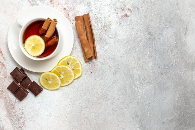 Vista dall'alto della tazza di tè con fette di limone e cioccolato sulla superficie bianca