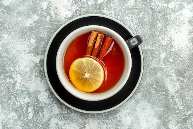 Vista dall'alto una tazza di tè con fette di limone e cannella sulla superficie grigia