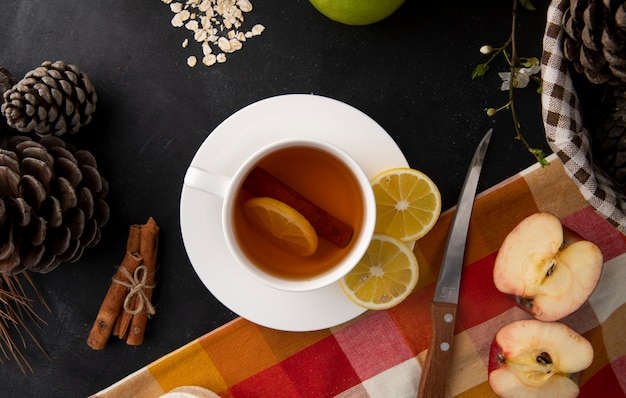 Top view cup of tea with lemon slices and cinnamon with apple halves and fir cones on the table