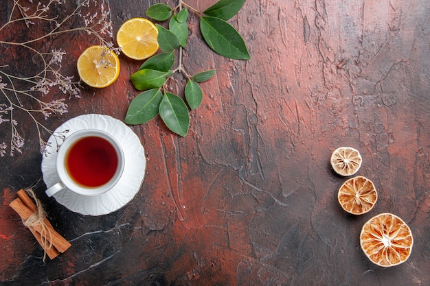 Top view cup of tea with lemon slices on dark table sugar tea photo biscuit sweet