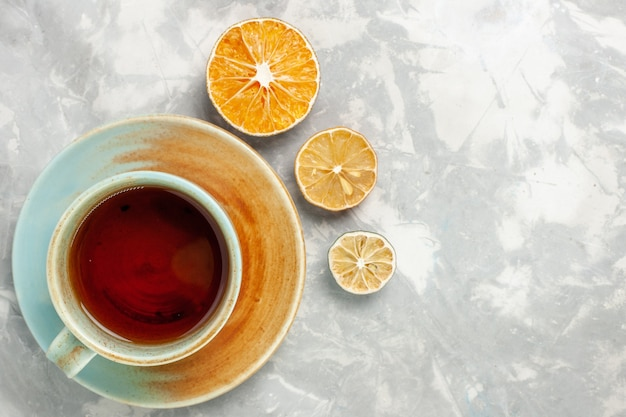Top view of cup of tea with lemon on white surface