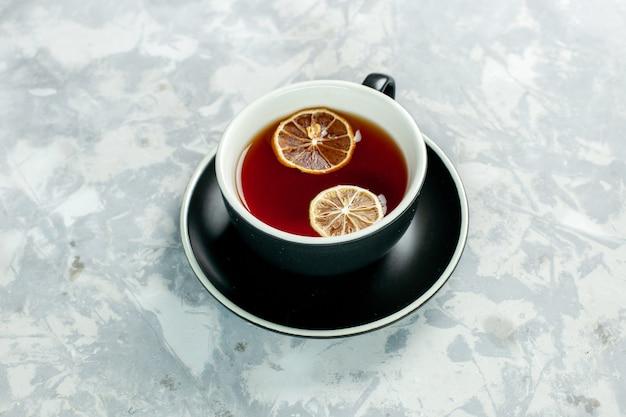 Vista dall'alto la tazza di tè al limone sulla parete bianca la bevanda del tè fiorisce il limone