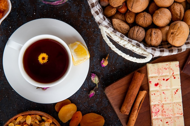 Top view of a cup of tea with lemon, with white chocolate bar, dried fruits and walnuts on black