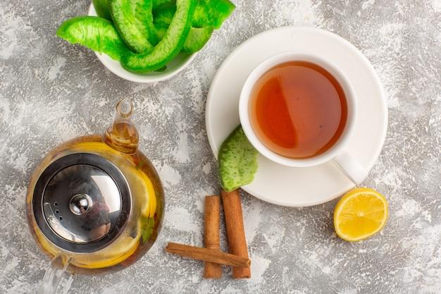 Vista dall'alto tazza di tè con limoni e cannella su superficie bianco chiaro