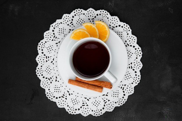 Top view of cup of tea with lemons and cinnamon on tea bag on paper doily on black surface