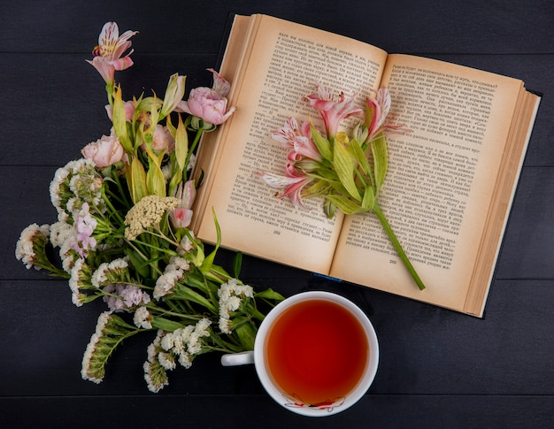 Top view of cup of tea with light pink flowers and an open book on a black surface