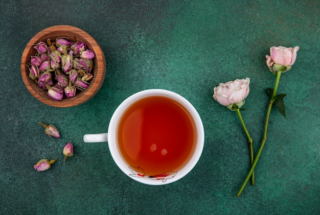 Top view of cup of tea with light pink roses and dried rose buds in a bowl on a green surface