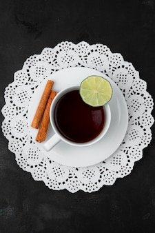 Top view of cup of tea with lime and cinnamon on tea bag on paper doily on black surface