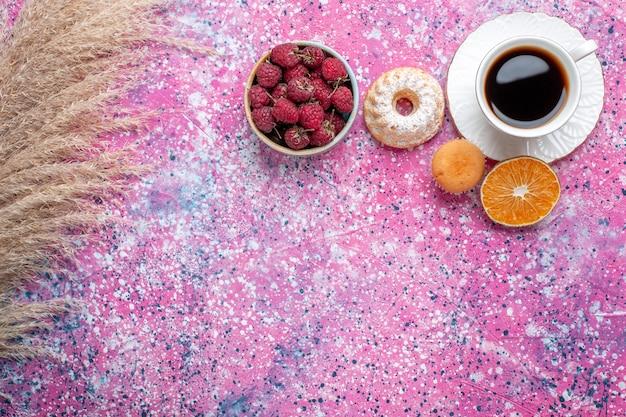 Vista dall'alto della tazza di tè con piccola torta e lamponi freschi sulla superficie rosa